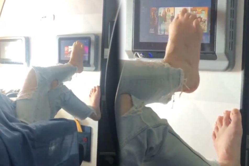 Schon mal was von Hygiene gehört? Frau bedient Flugzeugmonitor mit den Füßen