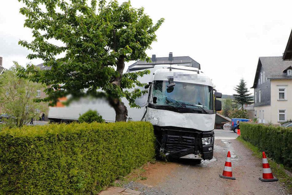 Grusel-Unfall: Ein Sattelschlepper zerstörte zwei Kleintransporter und einen Vorgarten.
