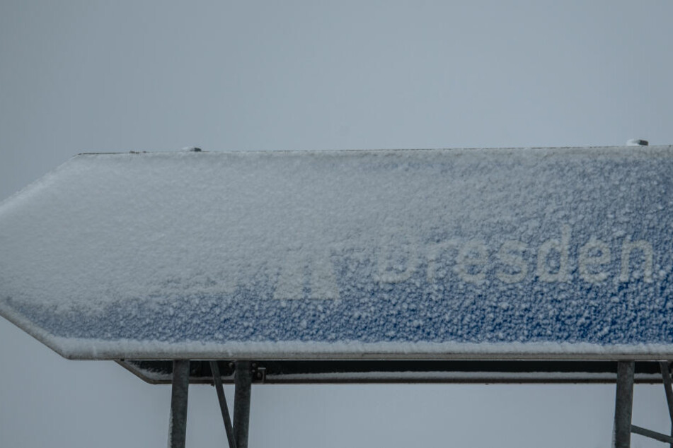 Ein Autobahnschild mit der Aufschrift Dresden an der Autobahn A17 wurde mit Schnee bedeckt. Bis nach Dresden selbst wird der Schnee in den nächsten Tagen allerdings nicht kommen.