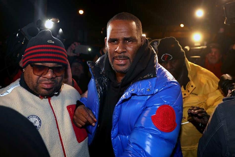 R. Kelly (M) steht vor dem Polizeirevier des 1. Bezirks. Der Sänger stellte sich noch am Freitagabend den Behörden in Chicago.