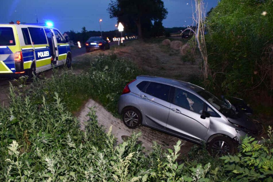 Ein Auto liegt nach einem Unfall im Graben neben der Fahrbahn der Bundesstraße 112.