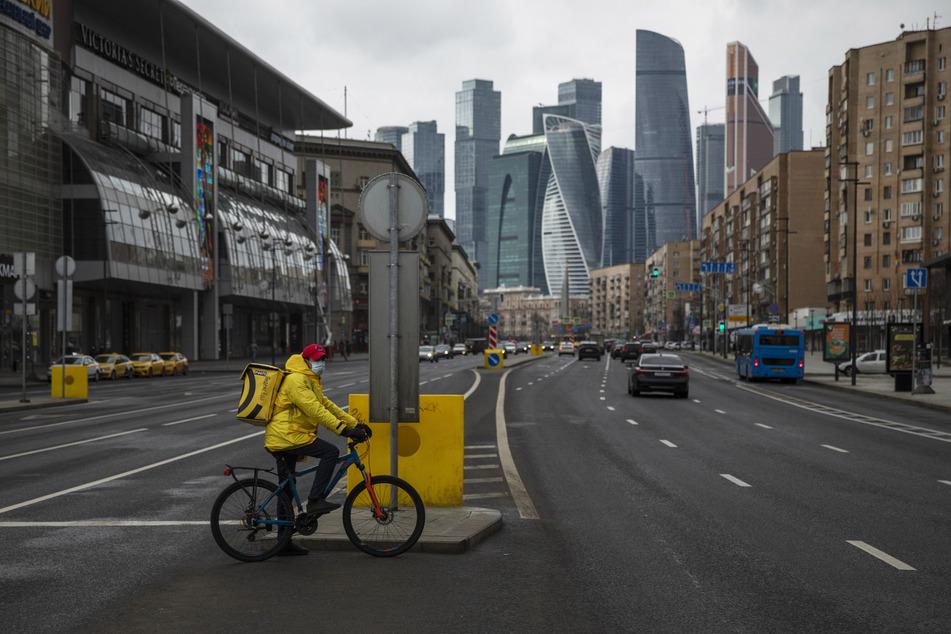 Ein Fahrradkurier mit einem Mundschutz und einer Transportbox auf dem Rücken überquert eine fast leere Straße. Seit der Verkündung der Ausgangsbeschränkungen boomt der Online-Einkauf von Lebensmitteln.