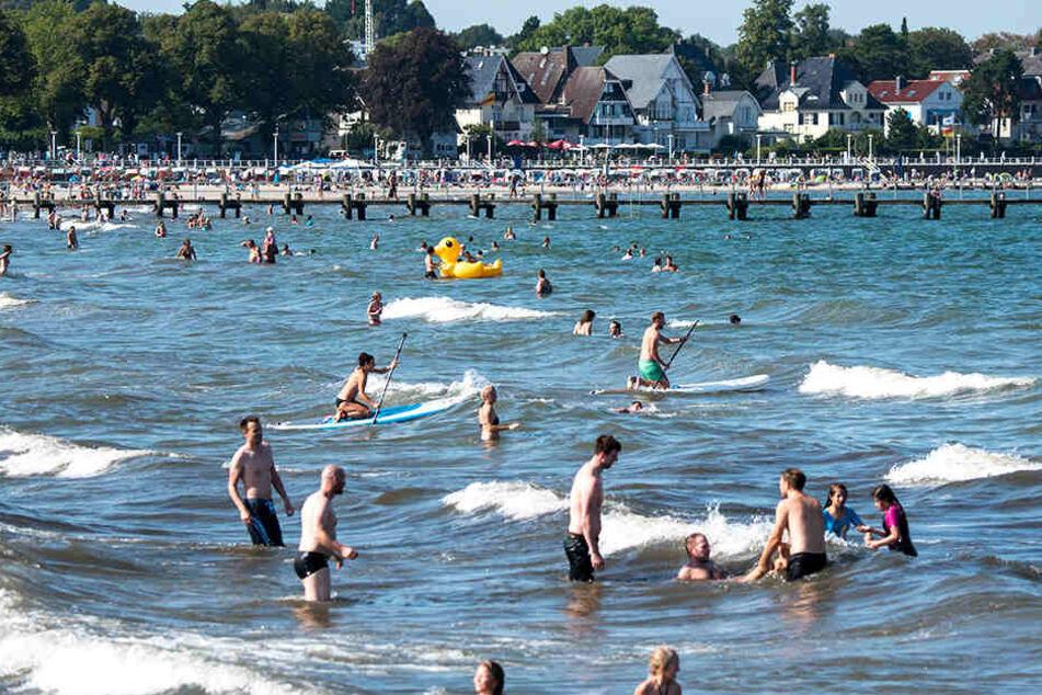 Bei herrlichem Sommerwetter baden Urlauber und Einheimische bei Travemünde in der Ostsee.