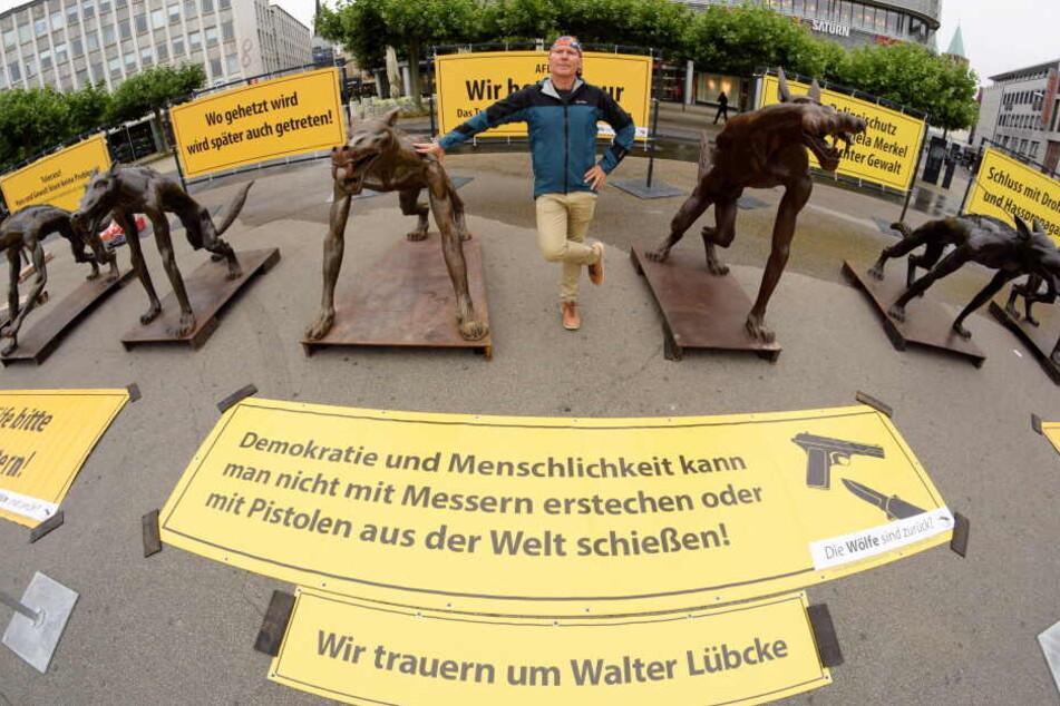 Der Brandenburger Künstler Rainer Opolka steht zwischen seinen Wolfsfiguren auf dem Kasseler Königsplatz.