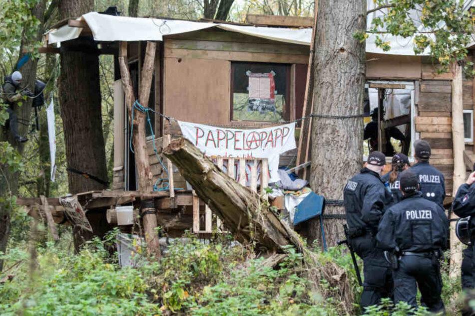 Polizisten stehen in dem Waldstück vor einem von Aktivisten gebauten Baumhaus.