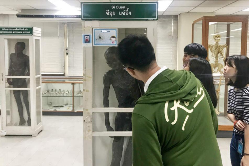Im Museum des Siriraj-Krankenhaus von Thailands Hauptstadt Bangkok betrachten Besucher den mit Paraffin einbalsamierten Leichnam des angeblichen Mörders Si Quey.