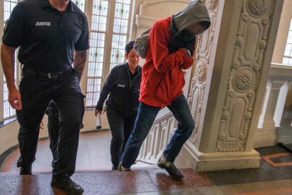 Der Angeklagte wird zum Prozessbeginn um den Mord an einem Rentner in Wittenburg zum Gerichtssaal geführt.