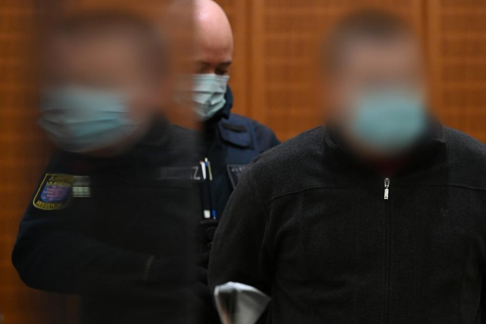 Der Angeklagte (r.) wird zu Beginn eines Mordprozesses von einem Justizbeamten in den Gerichtssaal des Landgerichts Frankfurt geführt. (Archivbild)