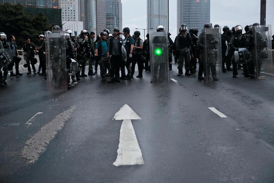 Ein Demonstrant richtet grünes Laserlicht auf einen Polizisten. Trotz des Verbots einer Großdemonstration kam es in der Sonderverwaltungszone erneut zu Protesten gegen die Regierung.