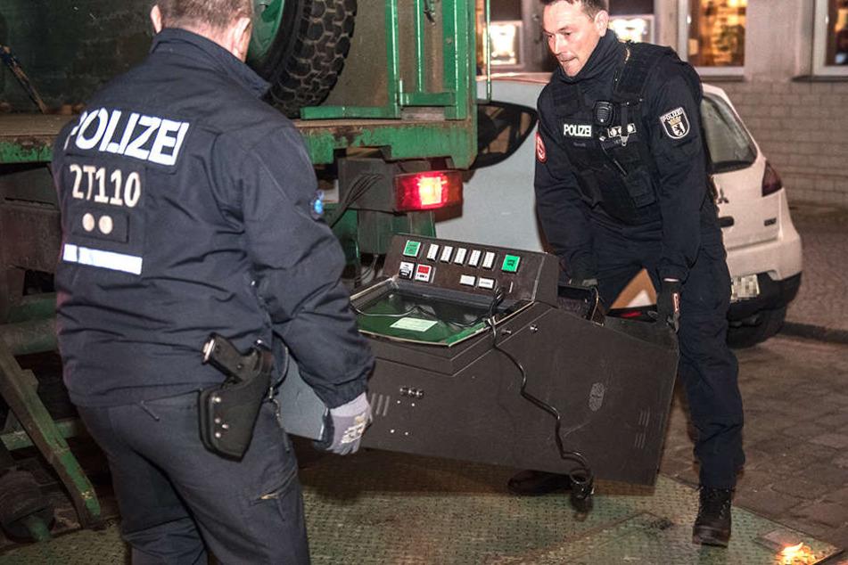 Zwei Polizisten beschlagnahmen einen Glücksspielautomaten.