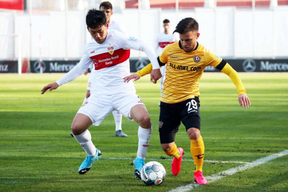 Dynamos Sascha Horvath im Zweikampf mit Stuttgarts Wataru Endo.