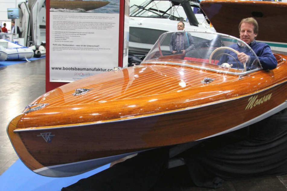 """Er zeigt den Klassiker-Schatz der """"Beach & Boat"""" - Dirk Maibuhr (51) sitzt in einer aufgearbeiteten Monsun aus dem Jahr 1963. Von dem Mahagoniboot wurden in der DDR nur zehn Exemplare gebaut."""