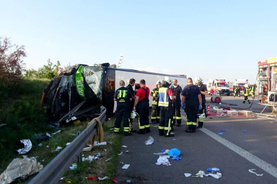 Rettungskräfte stehen vor dem umgekippten Flixbus. Insgesamt mussten 72 Verletzte versorgt werden.
