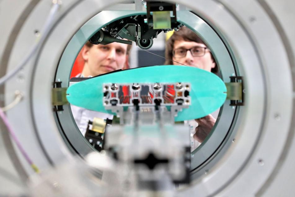 Die Entwickler Rainer Wallasch (l) und Ramon Tirschmann bereiten einen Versuch auf ihrer Pilotanlage mit Orbitalwickeltechnologie an der TU Chemnitz vor.