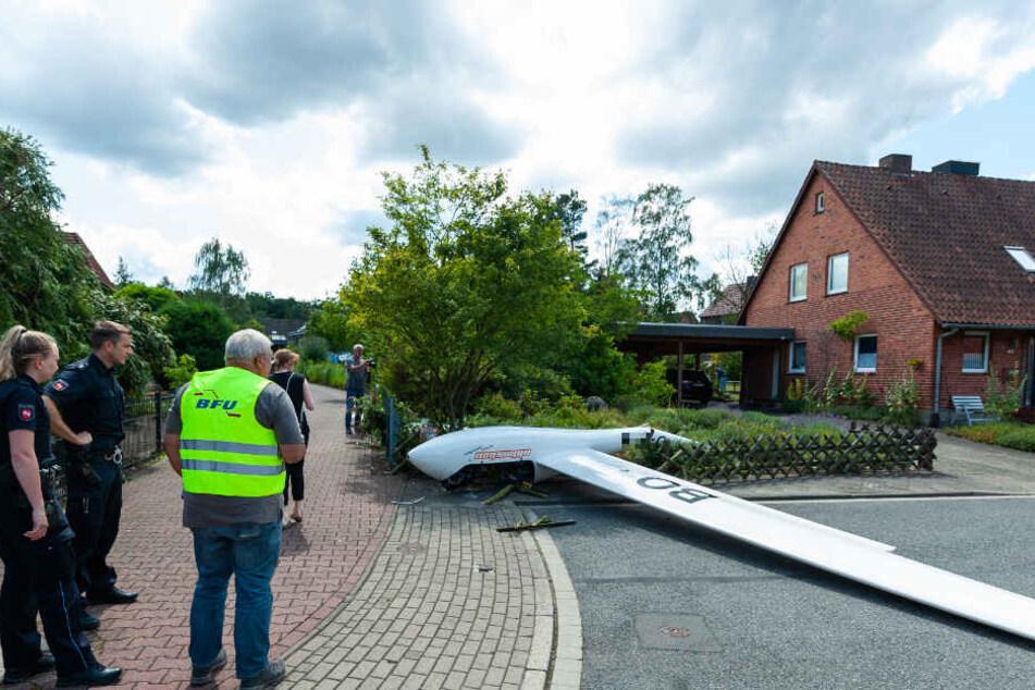 Das abgestürzte Segelflugzeug liegt in einem Vorgarten.