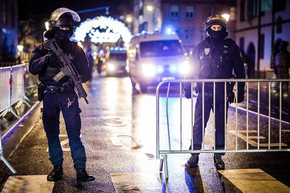 Schwer bewaffnet Polizisten stehen am abgesperrten Weihnachtsmarkt von Straßburg.