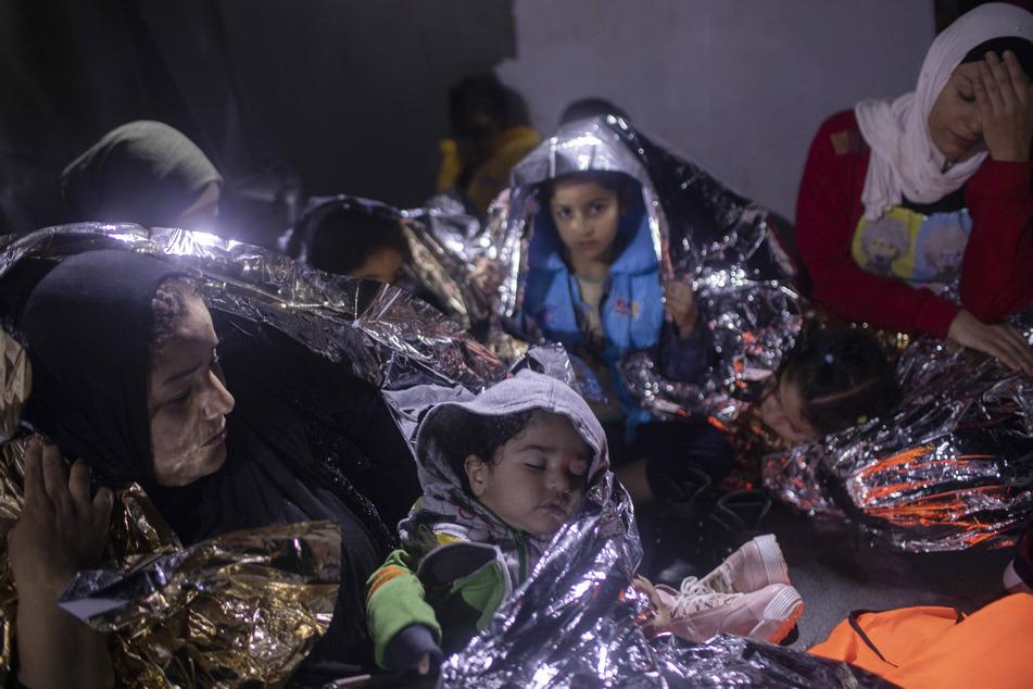 Migranten sitzen in Thermodecken gehüllt auf einem Schiff der griechischen Küstenwache. (Archivbild)
