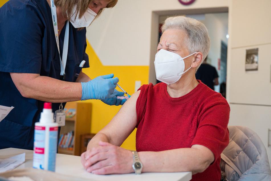Ein mobiles Impfteam impft eine Frau mit dem Biontech/Pfizer-Impfstoff.