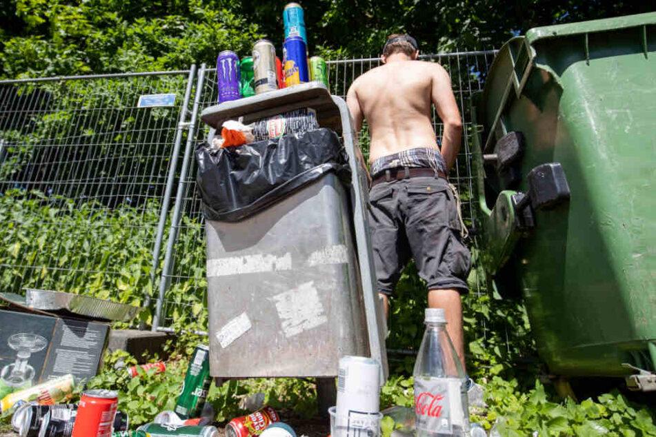 """Ein Besucher des Open-Air-Festivals """"Rock im Park"""" uriniert neben einem überfüllten Mülleimer auf dem Gelände."""