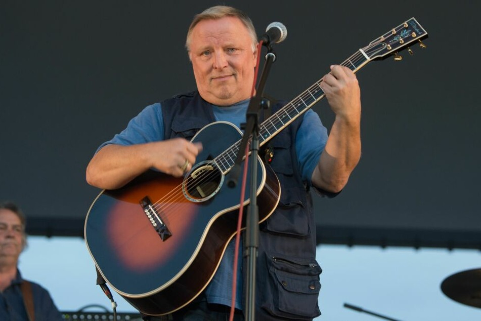 Axel Prahl steht während eines Konzerts mit seiner Gitarre auf der Bühne.