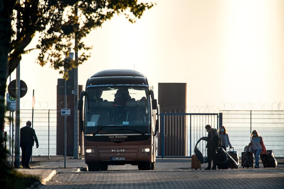 Besatzungsmitglieder des Kreuzfahrtschiffs «Mein Schiff 3» steigen am frühen Morgen am Terminal vor dem Kreuzfahrtschiff in Busse.