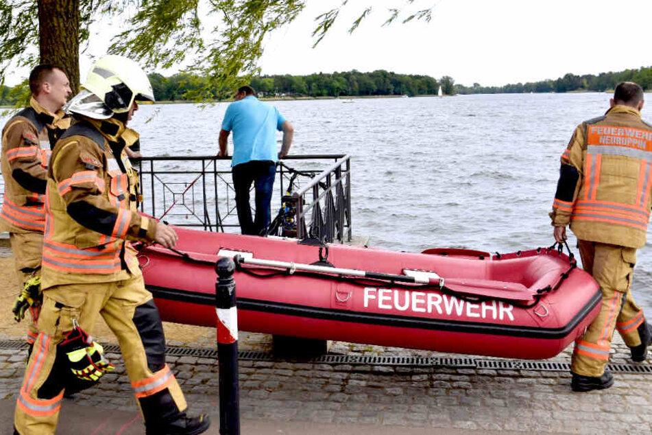 Einsatzkräfte der Feuerwehr tragen ein Schlauchboot in das Wasser.