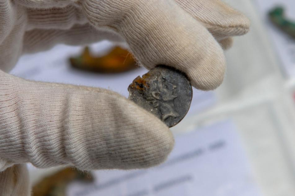Eine Mitarbeiterin der Stadtarchäologie hält eine gefundene Münze, auf der Kaiser Augustus abgebildet ist.