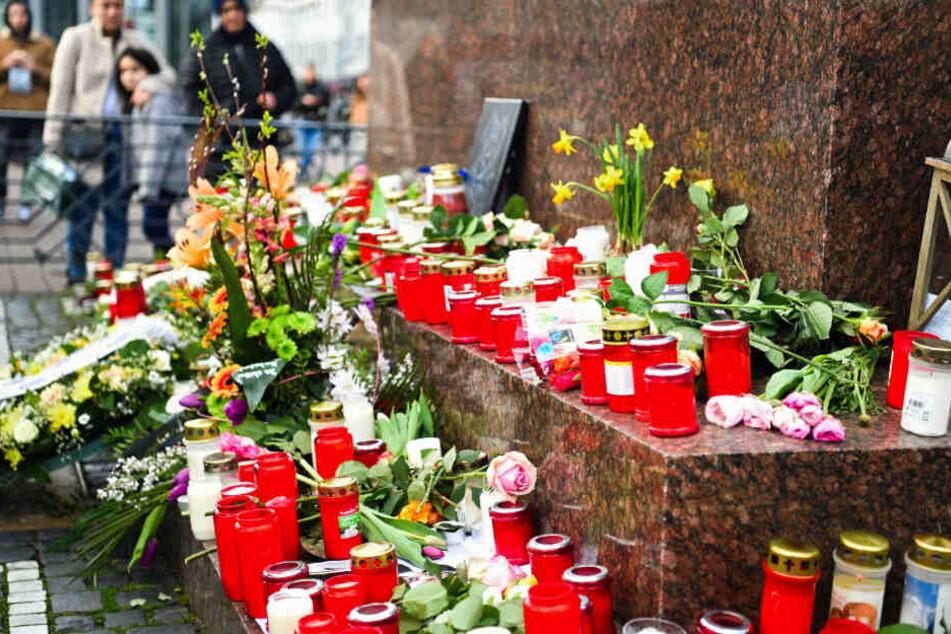 Hanau: Menschen haben am Brüder-Grimm-Denkmal Blumen und Kerzen niedergelegt.
