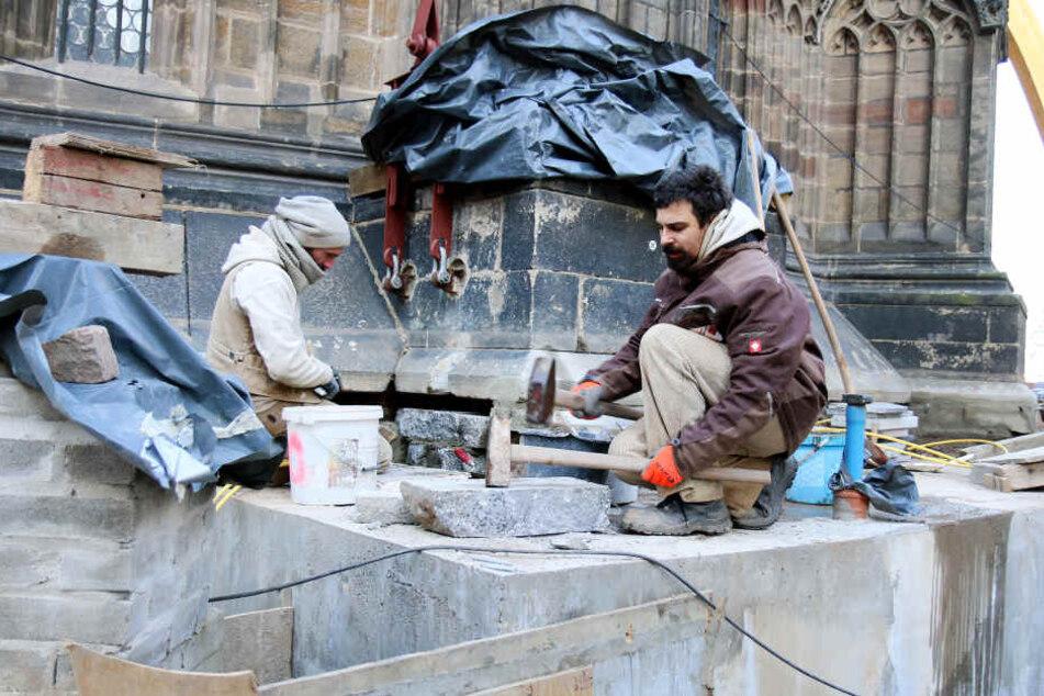 Die Steinmetzmeister Matthias Mehlhorn (l) und Sebastian Steinert sanieren ein altes Fundament am Dom in Zwickau, damit der Pfeiler an der Ostseite der Kirche wieder tragfähig wird.