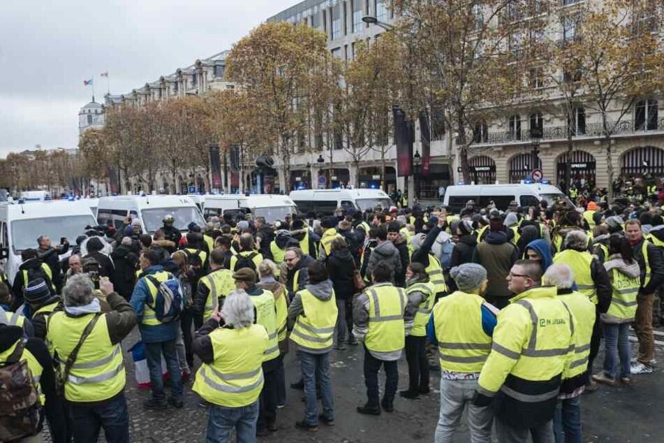 Demonstranten in gelben Warnwesten treffen auf der Champs-Elysees-Allee auf eine Barriere von Polizisten.