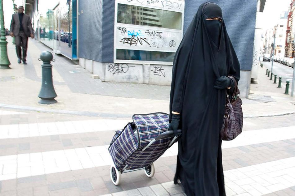 Mit einem Niqab bekleidet läuft eine Frau durch die Straßen.