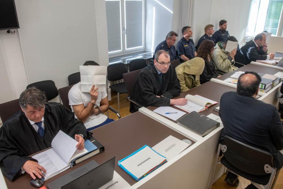 Vier Angeklagte sitzen neben ihren Anwälten im Verhandlungssaal des Amberger Amtsgerichts und verdecken ihre Gesichter.
