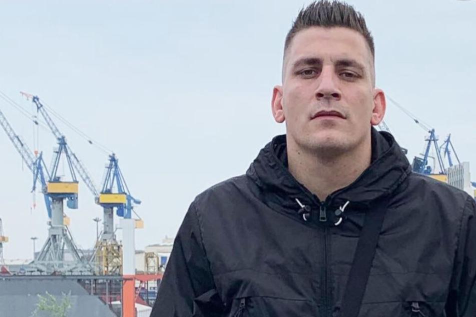 Rapper Gzuz posiert vor dem Hamburger Hafen.