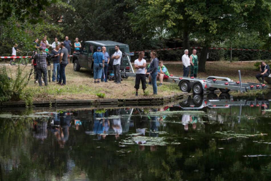 """Viele neugierige Zuschauer haben sich um den """"Tatort Teich"""" versammelt."""