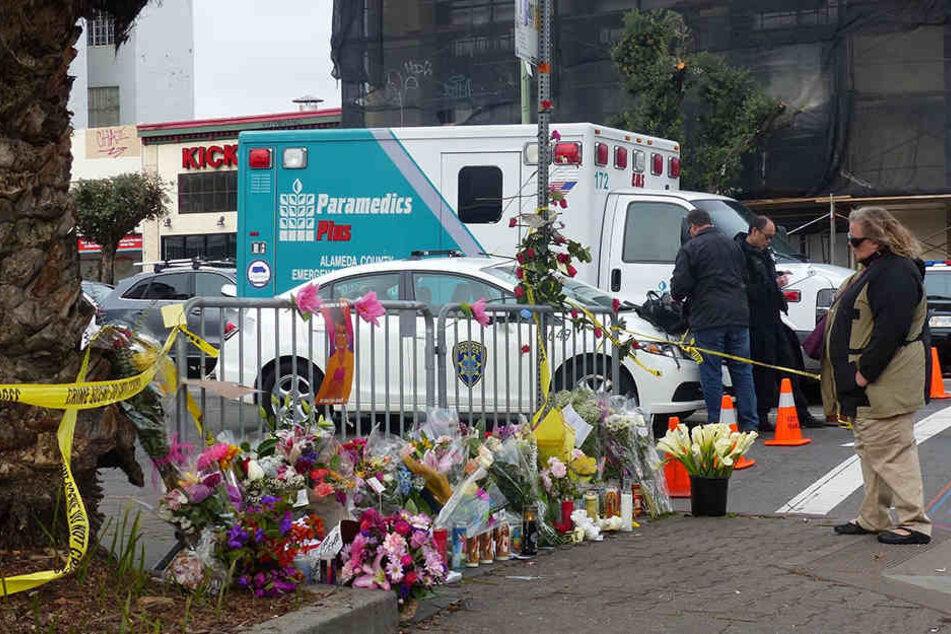 Hunderte Blumen und Andenken liegen auf dem Gehweg vor der ausgebrannten Lagerhalle.