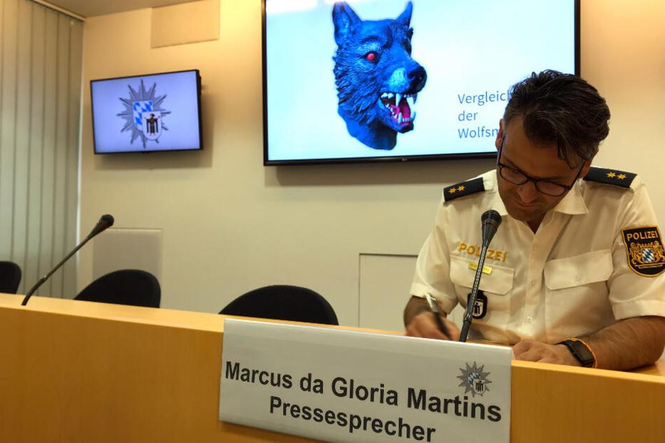 Marcus da Gloria Martins, Sprecher der Münchner Polizei, bei einer Pressekonferenz. Im Hintergrund ist ein Vergleichsbild der Wolfsmaske zu sehen.