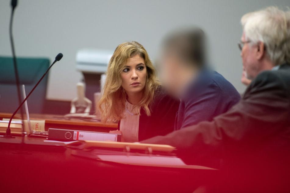 Der Angeklagte sitzt neben seinen Anwälten Louisa Krämer und Hans Holtermann im Landgericht.