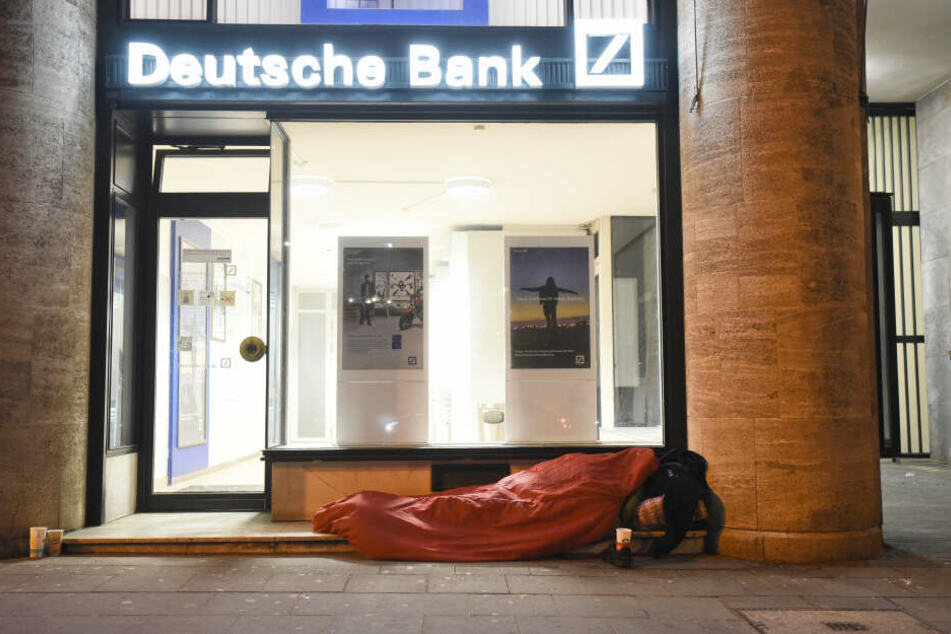 Ein Obdachloser schläft bei eiskalten Temperaturen vor einer Bankfiliale in Köln.