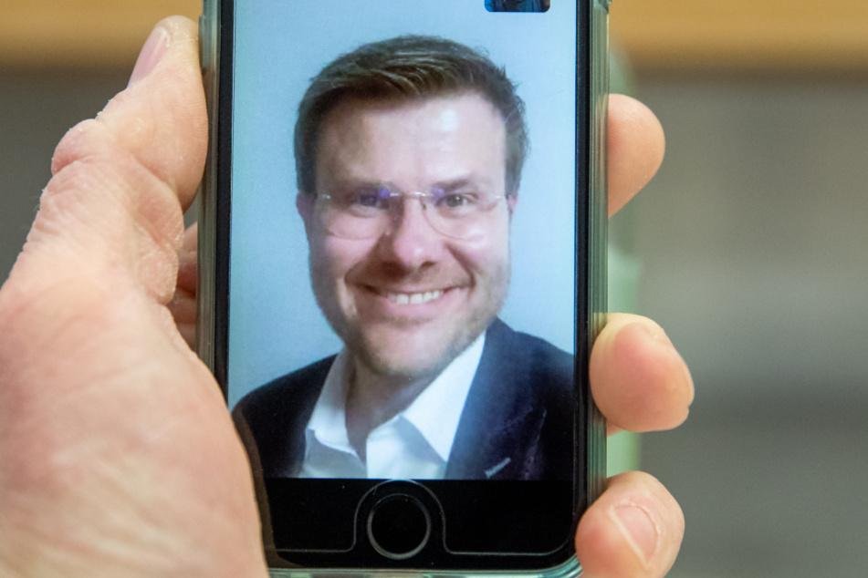 Marcus König, CSU-Spitzenkandidat für das Oberbürgermeisteramt in Nürnberg, lächelt per Video-Anruf nach den Ergebnissen der Auszählungen der Stichwahlen für die Kommunalwahl in die Kamera.
