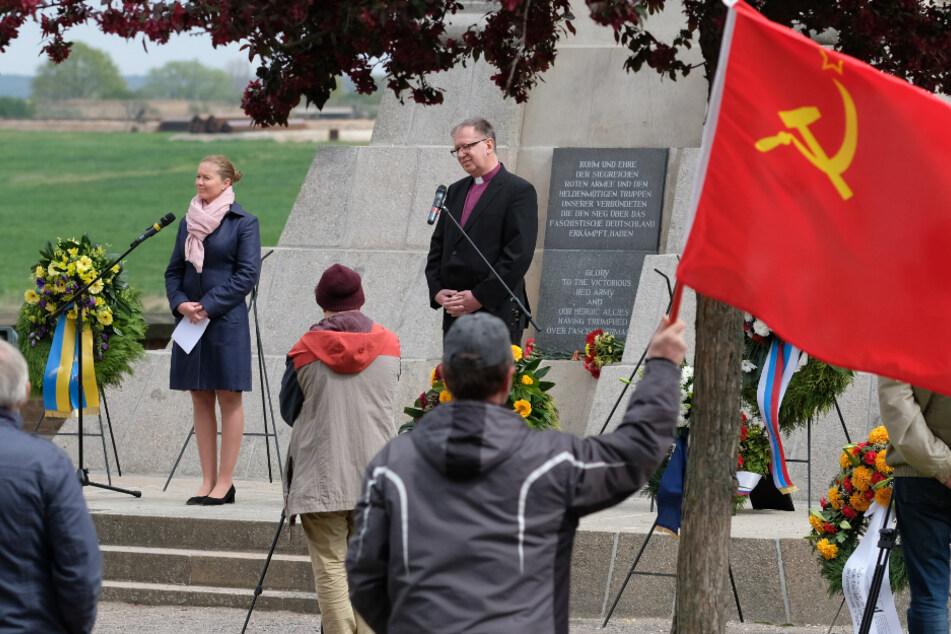 Torgaus Oberbürgermeisterin Romina Barth (CDU) und Johann Schneider, Regionalbischof Halle-Wittenberg der evangelischen Kirche in Mitteldeutschland, stehen am Denkmal der Begegnung, im Vordergrund hält ein Teilnehmer die Fahne der Sowjetunion.
