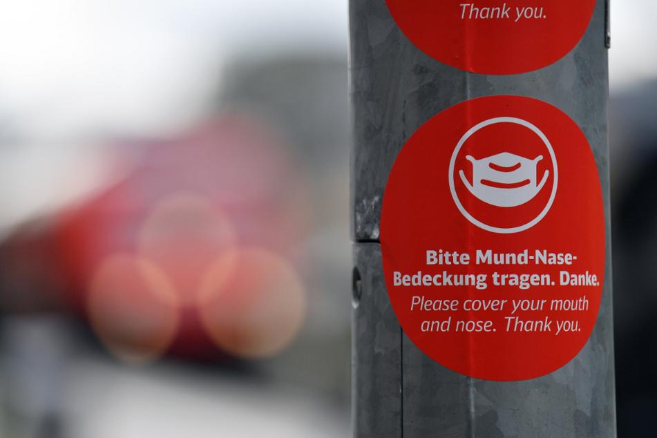 """""""Bitte Mund-Nase-Bedeckung tragen"""" steht in deutscher und englischer Sprache auf einem Aufkleber (Symbolbild)."""