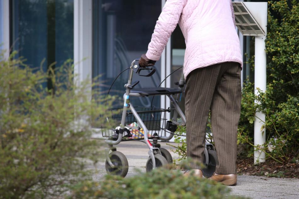 Ein ältere Frau mit Rollator geht vor dem Eingang des Seniorenheims in Würzburg.