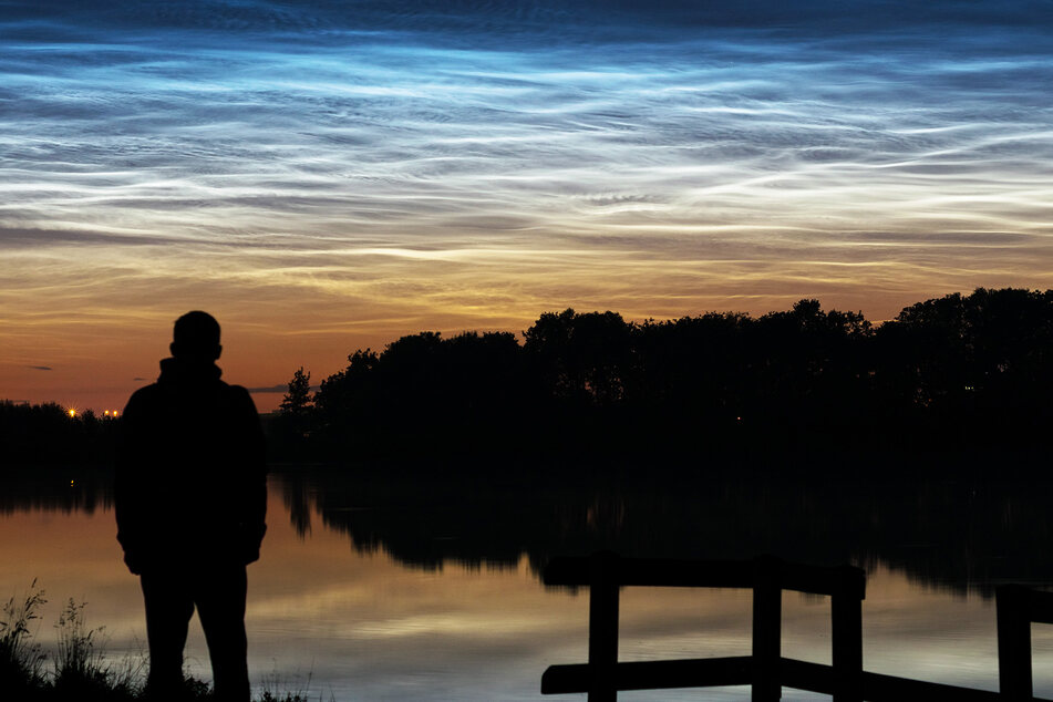 Ein Mann steht am See und schaut in den leuchtenden Nachthimmel.