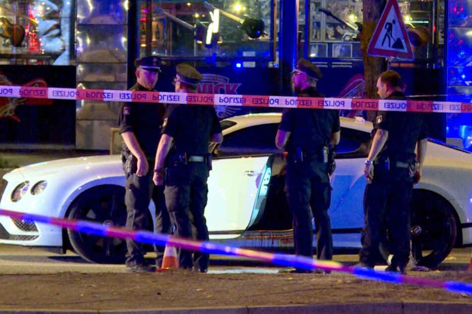 Polizisten stehen neben dem Auto des Opfers, nachdem Schüsse gefallen waren.