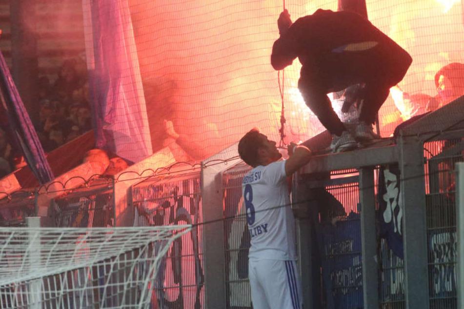 Spielunterbrechung wegen Pyrotechnik: HSV-Spieler Pierre-Lewis Holtby redet den Fans ins Gewissen.