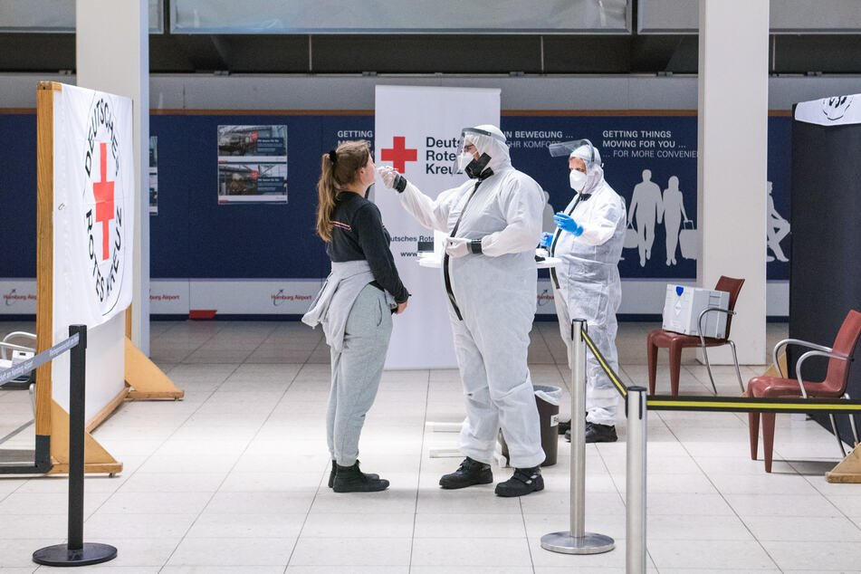Eine Reisende lässt am Hamburger Flughafen von einem Mitarbeiter des Deutschen Roten Kreuzes (DRK) einen Corona-Test machen.