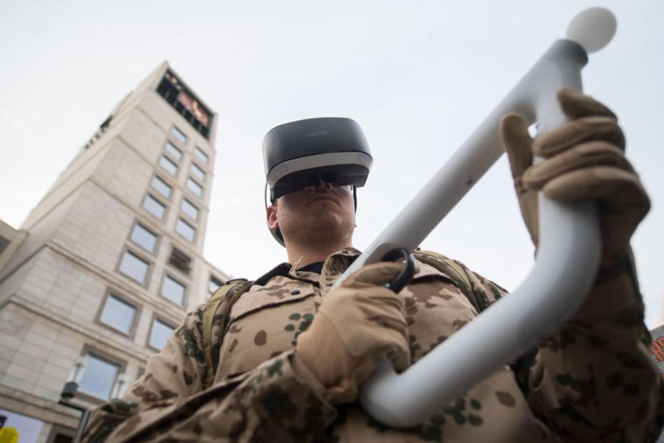 Ein Rüstungsgegner in Uniform hat vor dem Rathaus bei einer Kundgebung von Rüstungsgegnern gegen die Militärmesse ITEC eine Konsolenspielzeugwaffe in den Händen und eine VR-Brille auf dem Kopf.