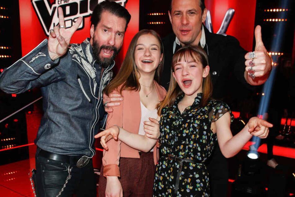 """Die Schwestern Mimi (l.) und Josefin freuen sich mit Coach Alec Völkel (l.) Sascha Vollmer (r.) von BossHoss beim Finale von """"The Voice Kids""""."""