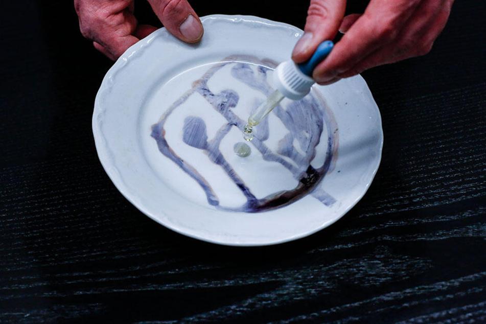 Mit Jod werden gespülte Teller auf noch vorhandene Essensreste getestet. Was sich verfärbt, ist noch schmutzig.