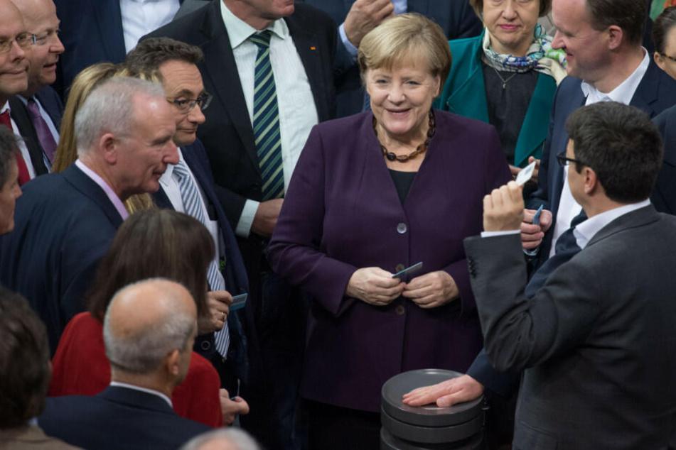 Bundeskanzlerin Angela Merkel (CDU) und weitere Abgeordnete stimmen bei der 128. Sitzung des Deutschen Bundestages namentlich ab.